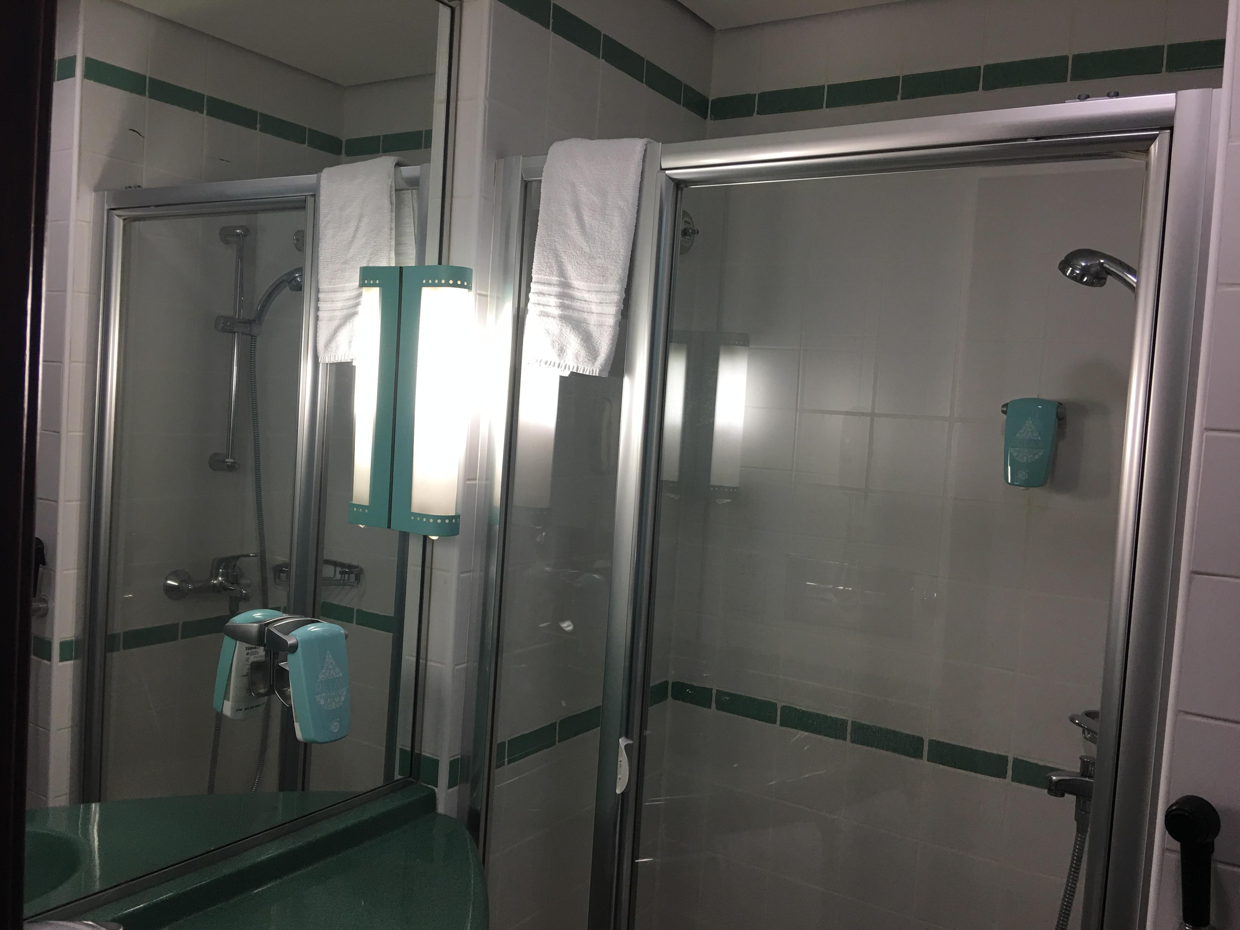 Das Bad ist recht eng, in der Ecke rechts befindet sich die Toilette. Es gibt einen Spender für Duschgel und Handwaschgel.