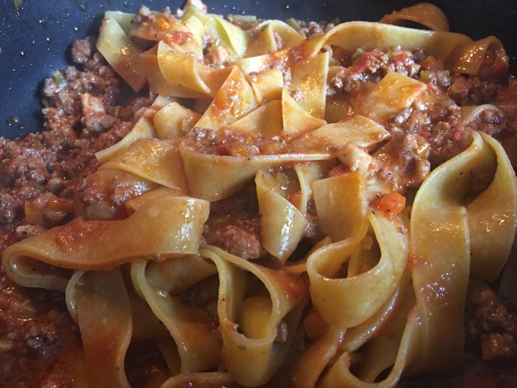 Ragù alla Bolognese. Die Pasta wird sobald sie fertig ist sehr heiß unter das Ragù gemischt und dann sofort serviert.
